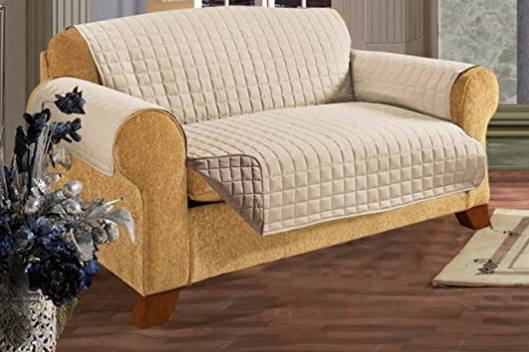 A large sofa covered with a beige furniture protector