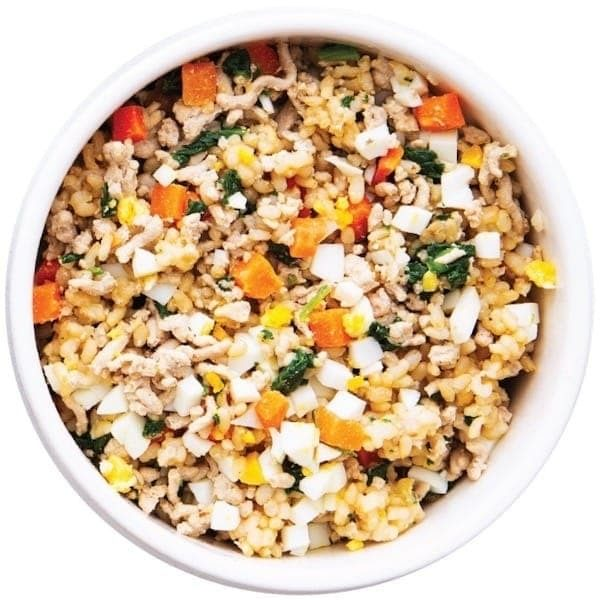 A bowl of fresh dog food full of veggies and protein-rich meats