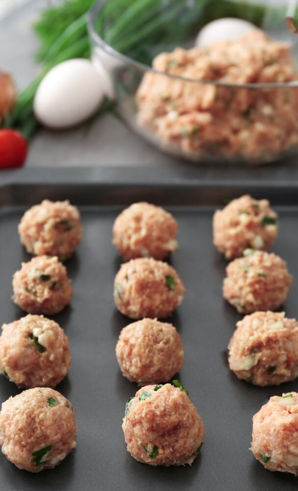 raw turkey meatballs lined on a baking tray ready for the oven
