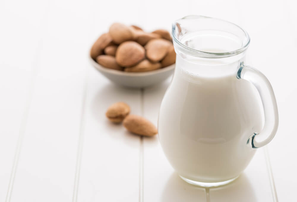 A jar of almond milk and whole almond kernels